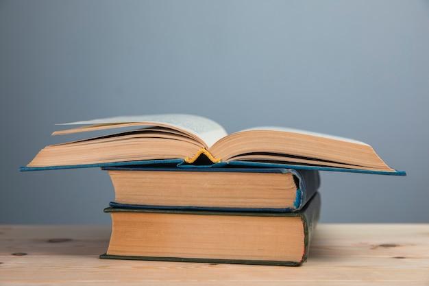 Bücher auf dem tisch an einer grauen wand