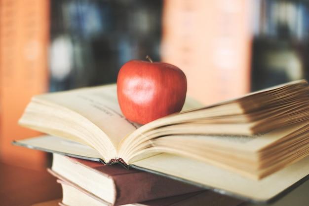 Bücher auf dem tisch in der bibliothek - bildung, die alten bücherstapel auf holzschreibtisch und verschwommenem bücherregalraumhintergrund mit apfel auf offenem buch lernt, zurück zum schulkonzept