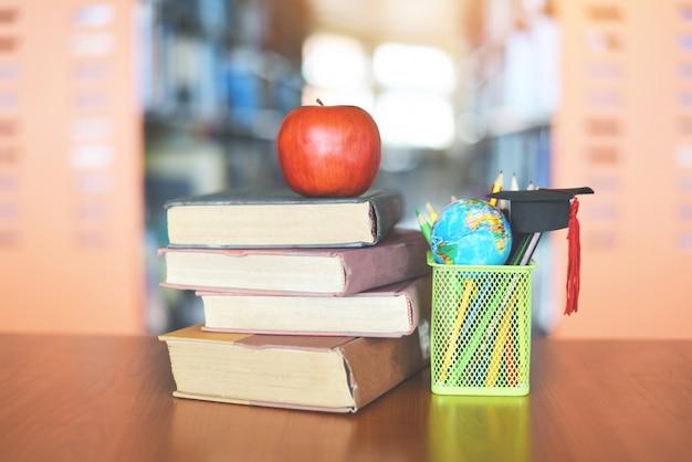 Bücher auf dem tisch in der bibliothek - bildung, die alten bücherstapel und abschlusskappe auf einem federmäppchen mit erdkugelmodell auf holzschreibtisch und verschwommenem bücherregalraum mit apfel auf buch lernt