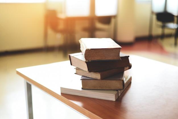 Bücher auf dem tisch in der bibliothek - bildungs-lernbuchstapel auf holzschreibtisch und verschwommenem raumhintergrund, zurück zum schulkonzept