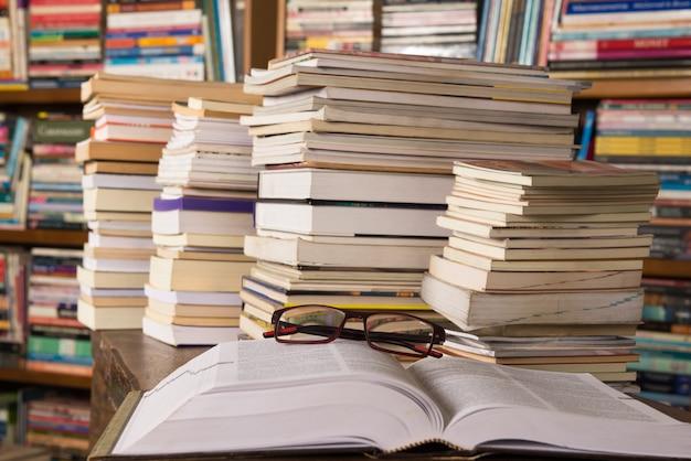 Bücher auf dem tisch und in bücherregalen