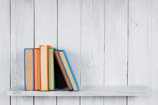 Bücher auf einem holzregal. auf einem hölzernen, weißen hintergrund.
