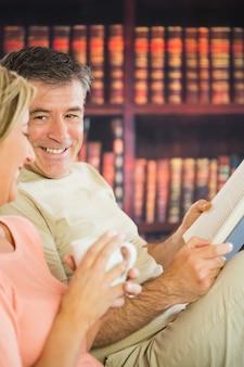 Bücher des glücklichen paars lese und trinkender kaffee in einem lesesaal