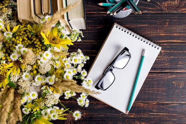 Bücher, gläser, markierungen und ein blumenstrauß in einer vase auf weiß