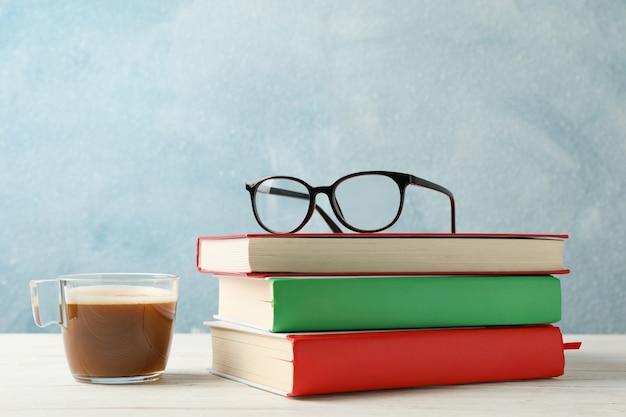 Bücher, gläser und eine tasse kaffee gegen blauen raum, platz für text