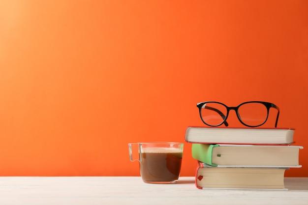 Bücher, gläser und eine tasse kaffee gegen orangefarbenen raum, platz für text