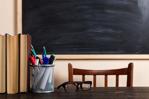 Bücher, kugelschreiber, bleistifte und gläser auf einem holztisch gegen eine kreidetafel.