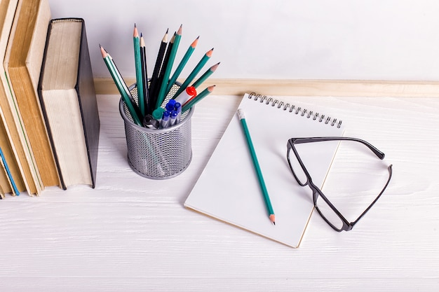 Bücher, markierungen, notizbuch, bleistift und gläser auf dem tisch