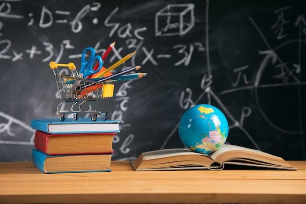 Bücher mit briefpapier und globus an bord hintergrund