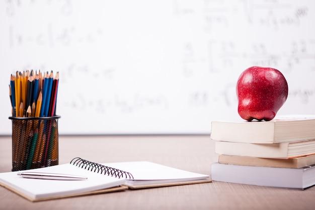 Bücher mit einem roten apfel oben, notizbuch und bleistifte auf dem tisch mit einer verschwommenen weißen tafel hinten. schulkonzept