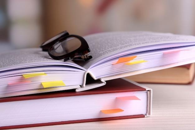 Bücher mit lesezeichen und gläsern auf dem tisch auf hell