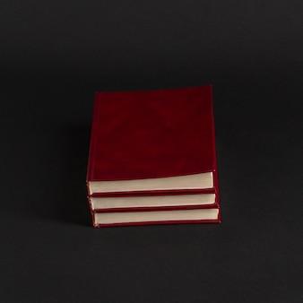 Bücher mit rotem einband auf schwarzem hintergrund, isoliert. zurück zur schule