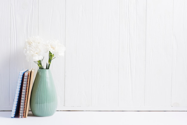 Bücher nahe den frischen blumen in der vase gegen gemalte hölzerne weiße tapete