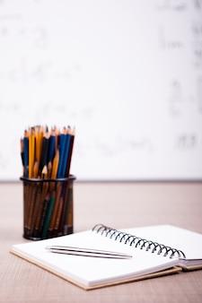 Bücher, notizbuch und bleistifte auf dem tisch mit einer verschwommenen weißen tafel auf der rückseite. schulkonzept
