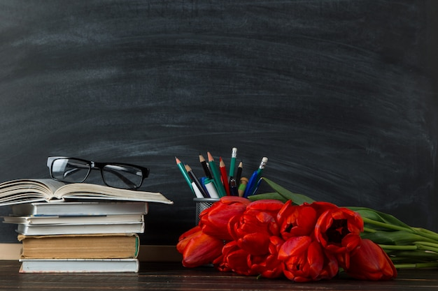 Bücher, rote tulpen und schulmaterial an der tafel