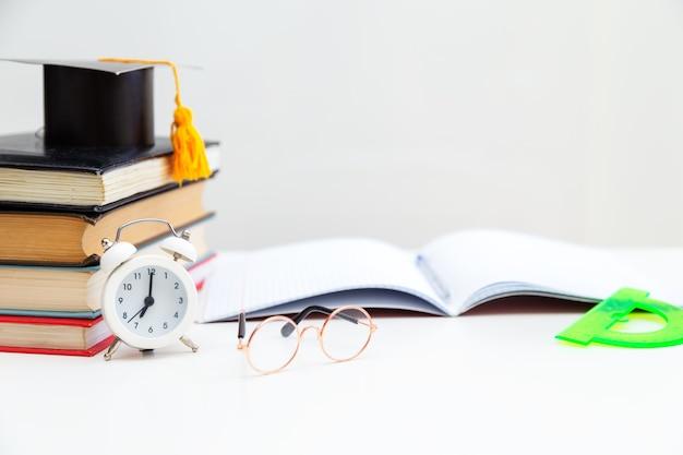 Bücher, schreibmaterial, brille, notizbuch und wecker auf dem desktop. zurück zur schule. lern- und selbstbildungskonzept.