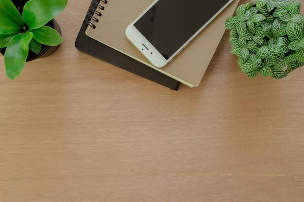 Bücher, smartphone und baumtopf auf rustikalem braunem hölzernem schreibtisch.