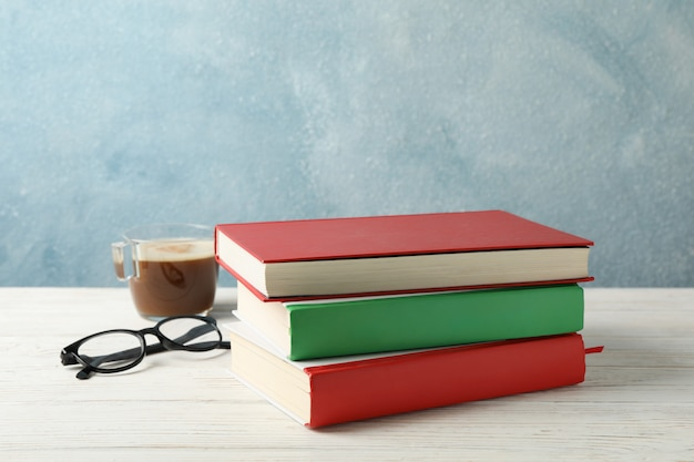 Bücher, tasse kaffee und gläser auf holztisch, platz für text