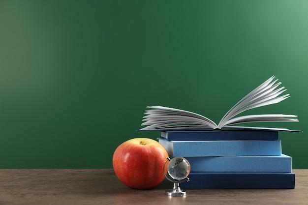 Bücher und apfel auf tafelhintergrund