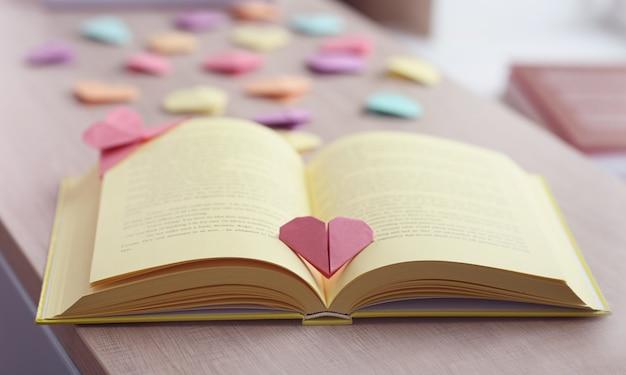 Bücher und herzförmige lesezeichen auf einem holztisch