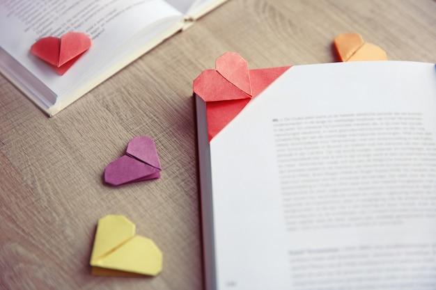 Bücher und herzförmige lesezeichen auf hellem holzhintergrund