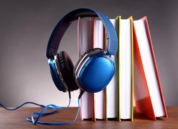 Bücher und kopfhörer als hörbuchkonzept auf grauem hintergrund