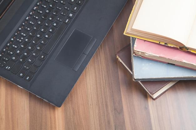 Bücher und laptop auf dem holztisch internet education business