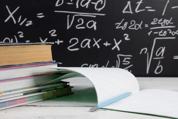 Bücher und notizbuch auf tafelhintergrund mit mathematischen formeln