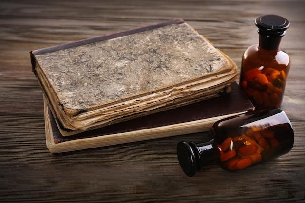 Bücher und pillen auf holztischnahaufnahme