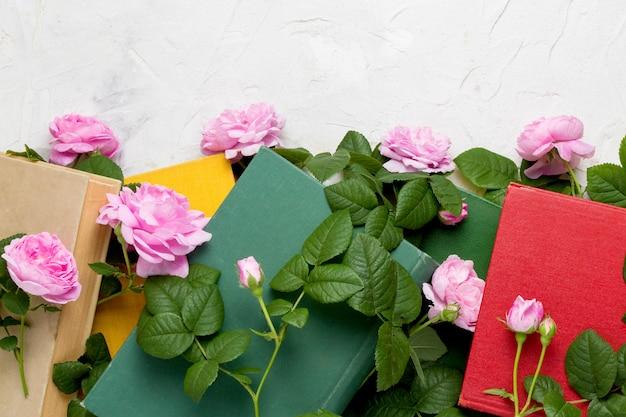 Bücher und rosen auf einer hellen steinoberfläche. konzeptbücher über liebe und romantische romane. flachgelegt, draufsicht