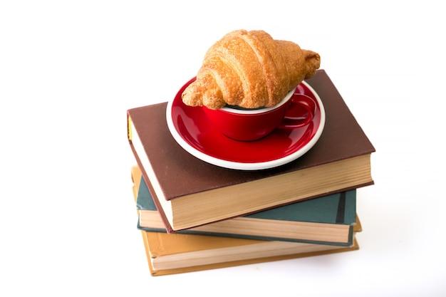 Bücher und rote tasse kaffee mit croissant auf weißem hintergrund