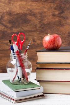 Bücher und schuleinzelteile mit hölzernem hintergrund