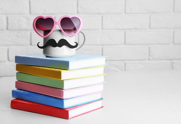 Bücher und tasse mit schnurrbart auf holztisch auf ziegeloberfläche