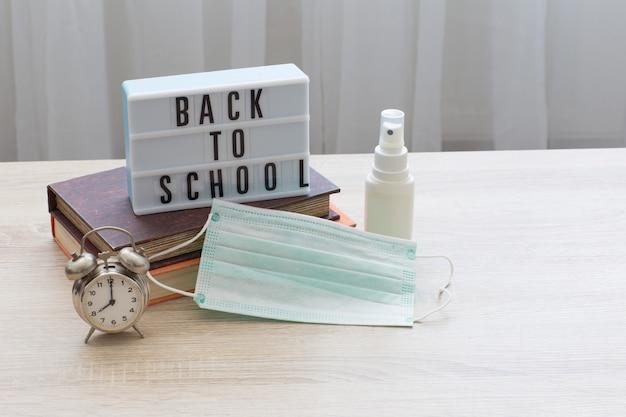 Bücher, wecker, die inschrift zurück in die schule, ein gesichtsschutz und ein händedesinfektionsmittel