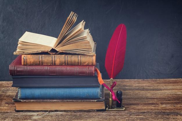 Bücherregal aus holz mit einem stapel antiker bücher und einem roten federstift, retro getönt