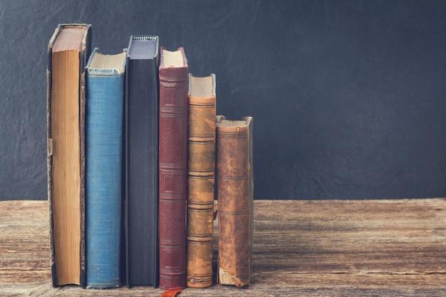 Bücherregal aus holz mit einer reihe antiker bücher, retro getönt