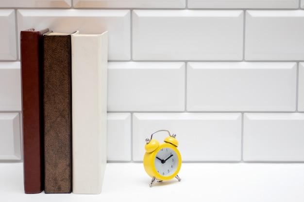 Bücherregal mit leeren büchern und gelbem wecker auf weißer backsteinmauer.
