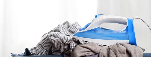 Bügeleisen und hemd auf bügelbrett in der wäscherei