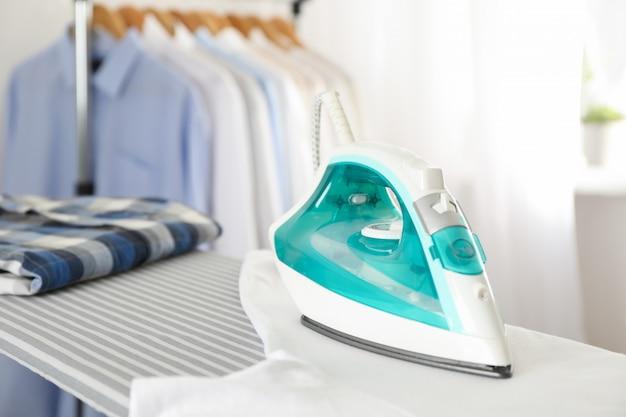 Bügeleisen und hemd auf bügelbrett,