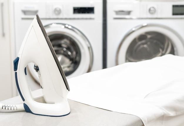 Bügeln sie auf bügelbrett mit weißem hemd in der waschküche