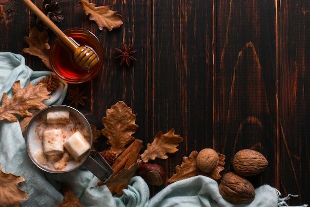 Bügeln sie becher mit kakao, honig, eibischen, gewürzen, auf einem hintergrund eines schals, trocknen sie blätter auf einem holztisch. herbststimmung, ein wärmendes getränk. copyspace.