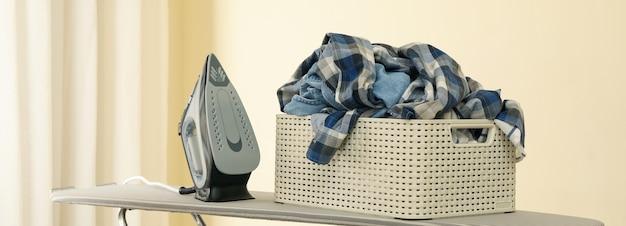 Bügeln und korb mit kleidung auf bügelbrett