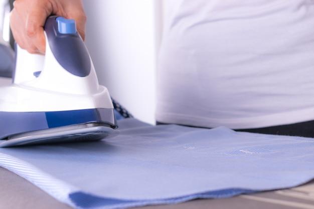 Bügelnde kleidung der nahaufnahmefrau auf bügelbrett in der waschküche zu hause.