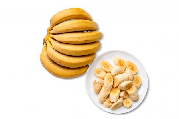 Bündel banane und banane geschält und in stücke geschnitten auf platte lokalisiert auf weißem hintergrund.