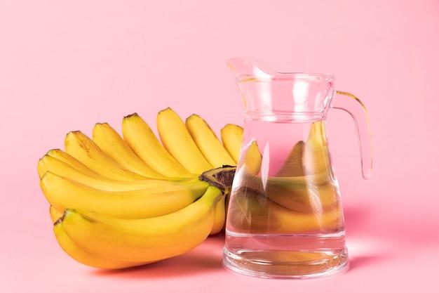 Bündel bananen mit krug wasser