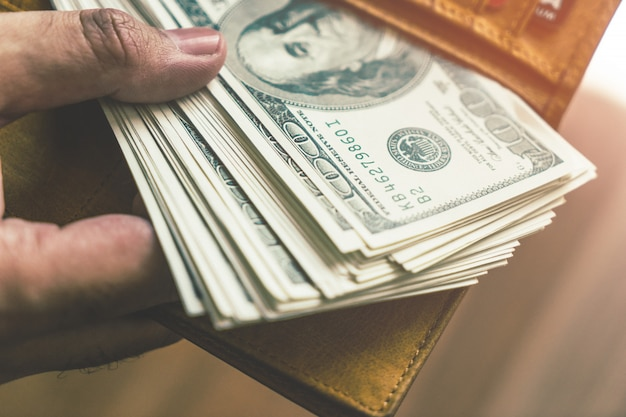 Bündel banknoten, die von der mappe herausnehmen