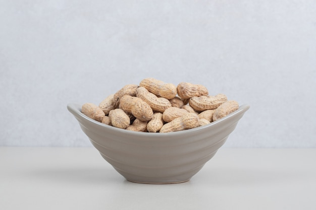 Bündel bio-erdnüsse in keramikschale