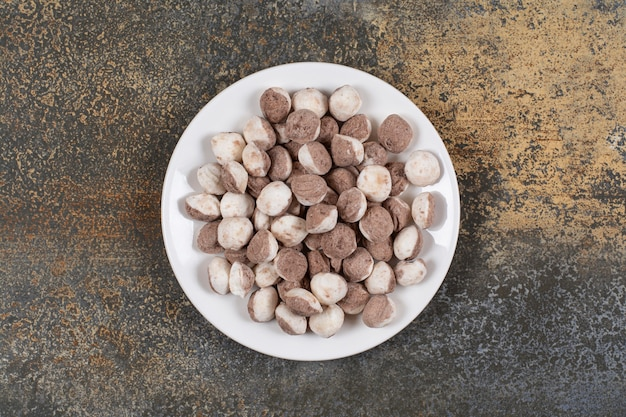 Bündel braune bonbons auf weißem teller.