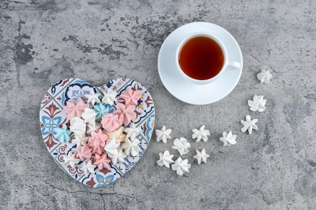 Bündel bunte baiser-bonbons auf herzförmigem untersetzer und tasse tee.