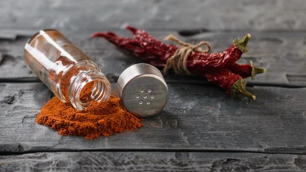 Bündel chilischoten und ein glas gemahlene paprika auf dem landtisch